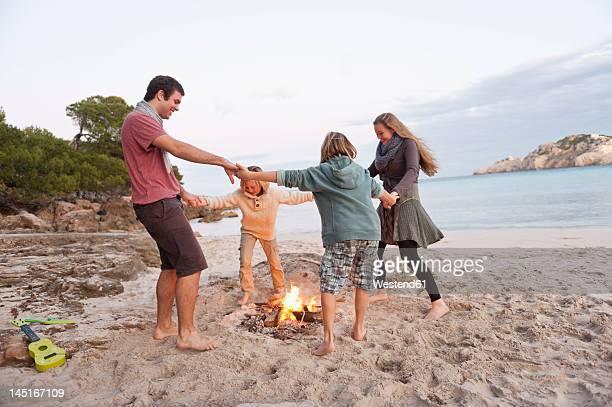 Spain, Mallorca, Friends dancing at camp fire on beach