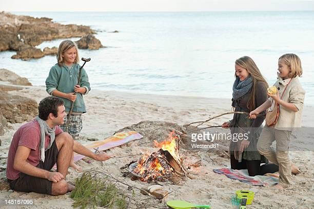 Spain, Mallorca, Friends grilling sausages at camp fire on beach