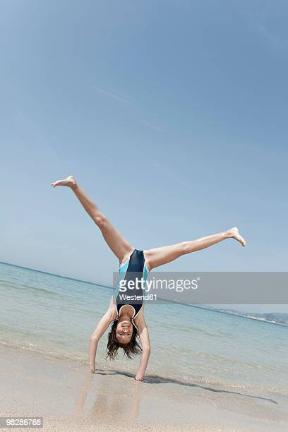 Spain, Mallorca, Girl (10-11) doing handstand on beach