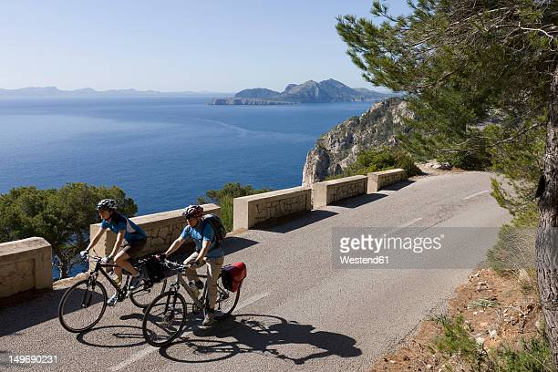 Spain, Mallorca, Man and woman cycling on road at Cap de Formento
