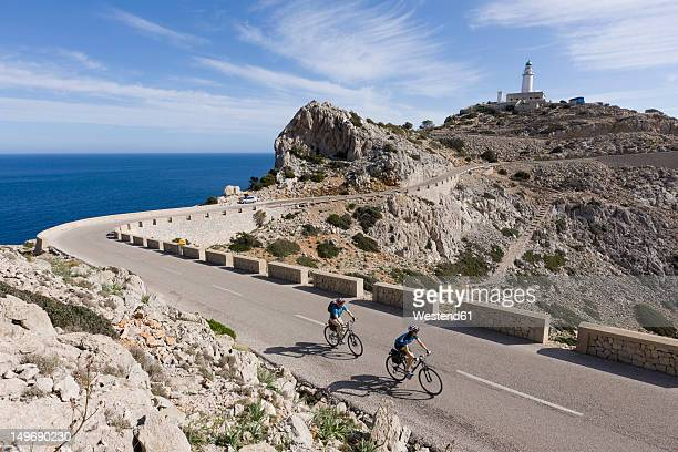 Spain, Mallorca, Man and woman cycling on road at Cap de Formentor