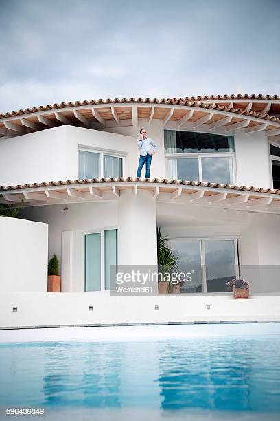 Spain, Mallorca, man standing on roof of his house telephoning