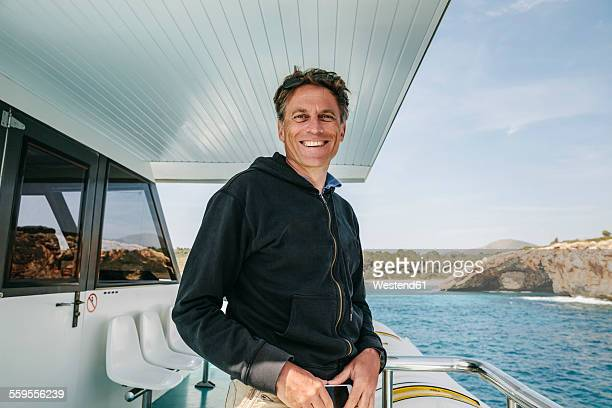 Spain, Mallorca, portrait of smiling man standing on a boat