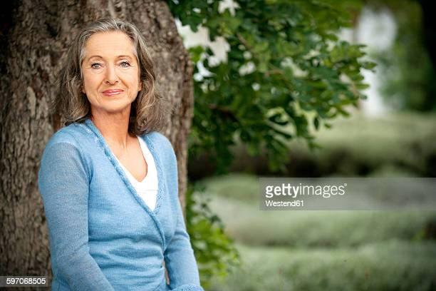 spain, mallorca, portrait of smiling mature woman in front of a tree in the garden - 55 59 años fotografías e imágenes de stock