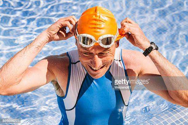 Spain, Mallorca, Sa Coma, smiling triathlet swimmer standing in a pool