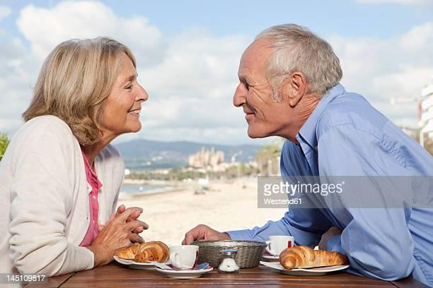 Spain, Mallorca, Senior couple in restaurant at beach, smiling