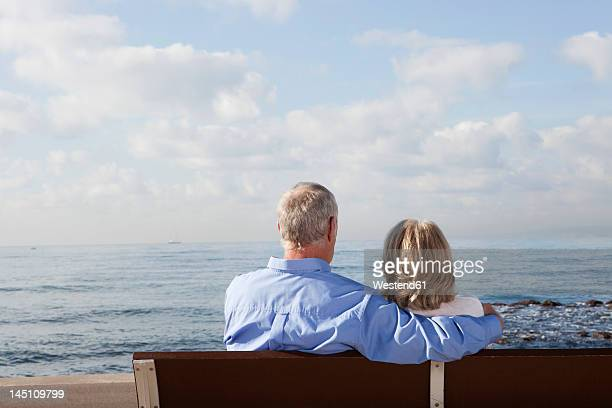 Spain, Mallorca, Senior couple sitting on bench at sea shore