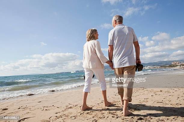 spain, mallorca, senior couple walking along beach - rolled up pants stock pictures, royalty-free photos & images