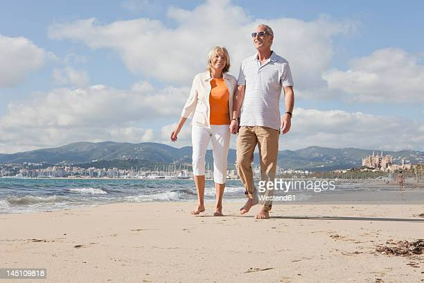 spain, mallorca, senior couple walking along beach, smiling - rolled up pants stock pictures, royalty-free photos & images