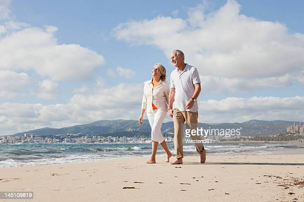 spain, mallorca, senior couple walking along beach, smiling - spain stock pictures, royalty-free photos & images