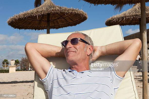 Spain, Mallorca, Senior man resting on deck chair at beach