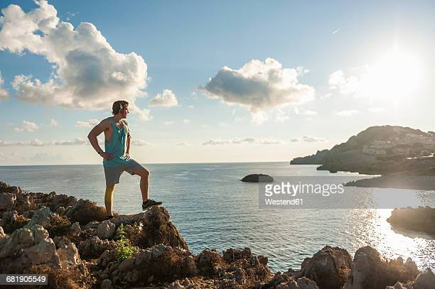 Spain, Mallorca, Sportsman standing on rocky coast in the morning