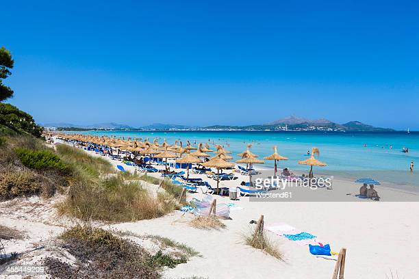 spain, mallorca, view of tourists in playa de muro beach - majorca stock pictures, royalty-free photos & images