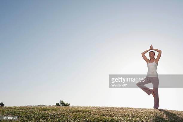 Spain, Mallorca, Woman excercising yoga, tree position