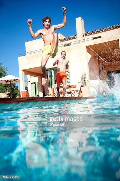 Spain, Mallorca, Young men jumping into swimming pool