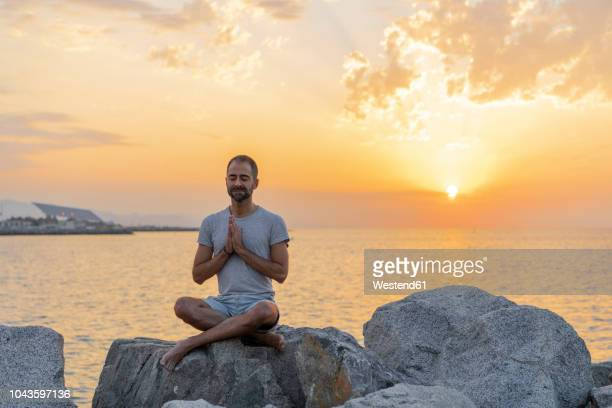 spain. man meditating during sunrise on rocky beach - yogi stock photos and pictures