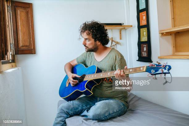 spain, man playing bass guitar in his room - only mid adult men stock pictures, royalty-free photos & images