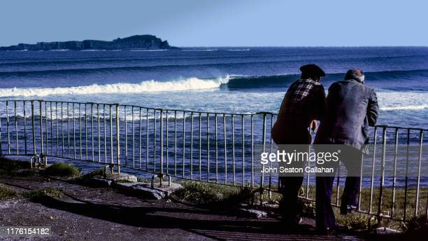 spain, men watching waves at mundaka - men stockfoto's en -beelden