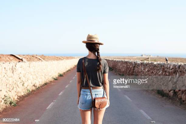 spain, menorca, back view of single traveller on county road - islas baleares fotografías e imágenes de stock