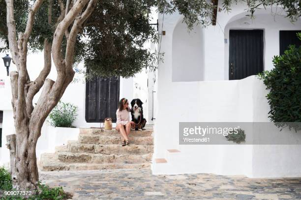 spain, menorca, bernese mountain dog sitted next to his owner in a small white village in summer - ミノルカ ストックフォトと画像