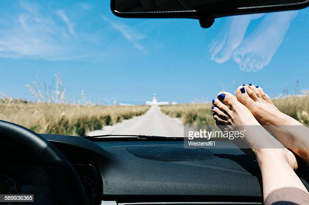 Spain, Menorca, feet on the dashboard, driving on empty road on vacations with a lighthouse in the background