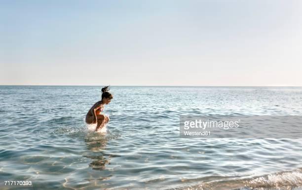 Spain, Menorca, girl jumping in the sea