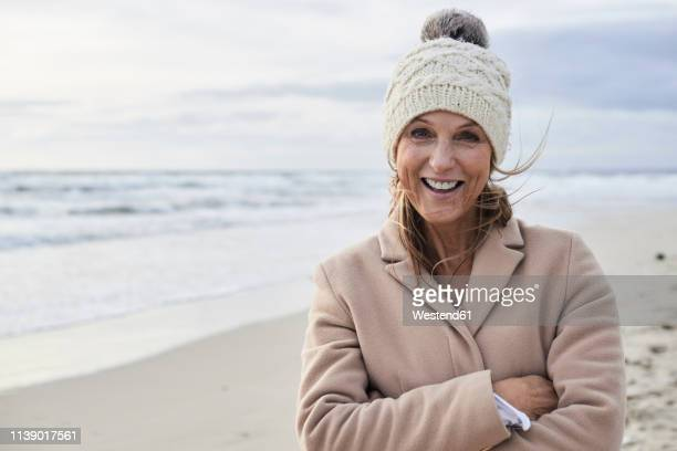 spain, menorca, portrait of happy senior woman on the beach in winter - knit hat stock pictures, royalty-free photos & images