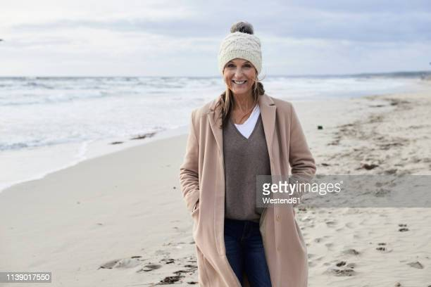spain, menorca, portrait of smiling senior woman wearing bobble hat and coat on the beach in winter - hands in pockets stock pictures, royalty-free photos & images