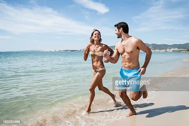 Spain, Mid adult couple running on beach