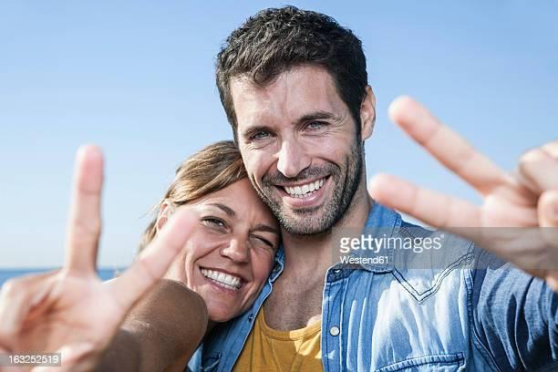 Spain, Mid adult couple showing peace sign, smiling, portrait