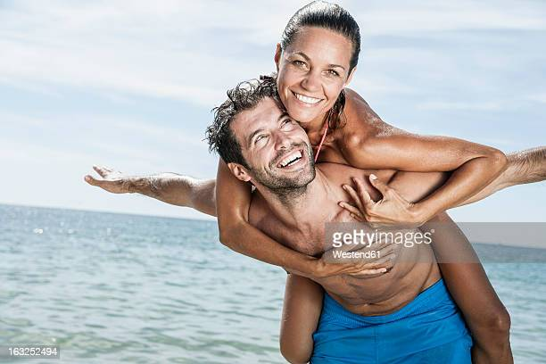 Spain, Mid adult man giving piggy back ride to woman
