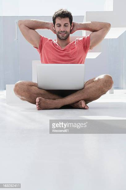 Spain, Mid adult man sitting on floor with laptop