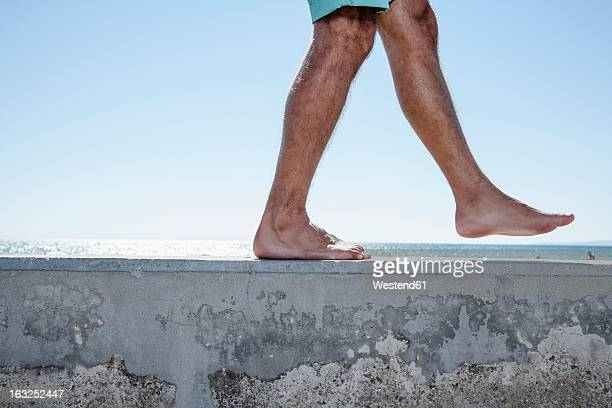 Spain, Mid adult man walking on wall