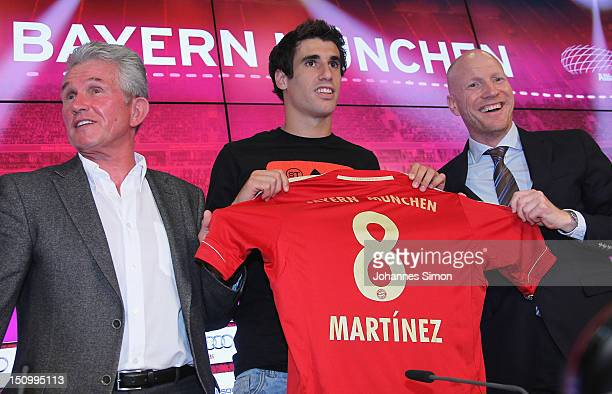 Spain midfielder Javi Martinez presents his new tricot number beside of FC Bayern head coach Jupp Heynckes and sport director Matthias Sammer during...