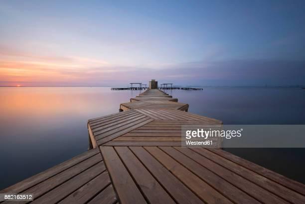 spain, murcia, mar menor, wooden pier at sunrise - murcia - fotografias e filmes do acervo