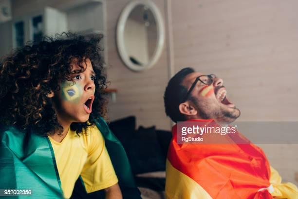 spanje nationale voetbal team aanhanger lachen en zijn vriendin ondersteuning van brazilië - brazil womens national football team stockfoto's en -beelden