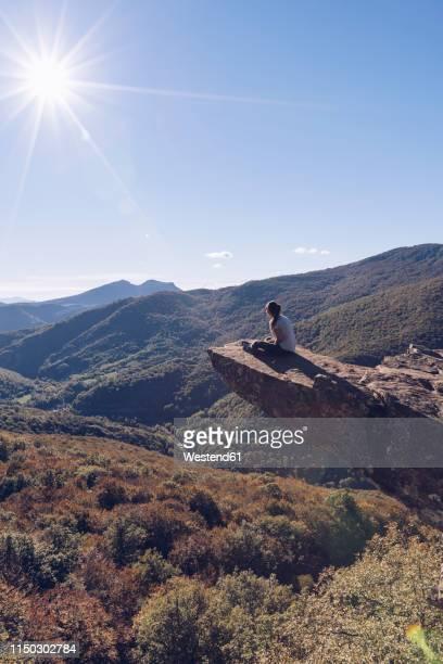 spain, navarra, irati forest, woman sitting on rock spur above forest landscape in backlight - comunidad foral de navarra fotografías e imágenes de stock