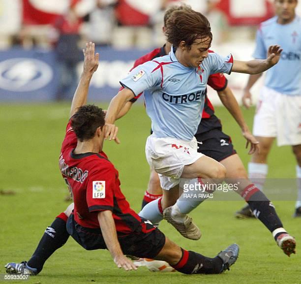 Osasuna's Jose Izquierdo tackles Celta's David Jimenez Silva, 16 October 2005, during a Spanish league football match at the Sadar stadium in...