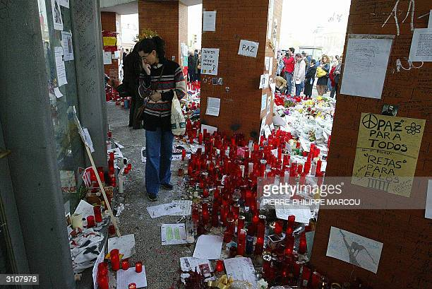 People gather around candles and flowers during a ceremony in memory of the victims of the blasts at Atocha train station 18 March 2004 in Madrid a...