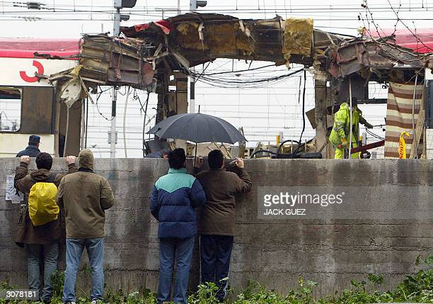 people watch forensic expert and rail workers inspecting the train which exploded the day before 12 March 2004 at the Atocha train station the day...