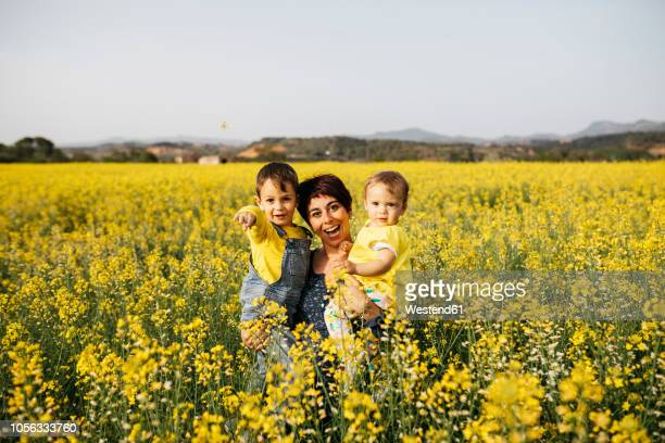 Spain, portrait of laughing mother with little son and daughter in a rape field