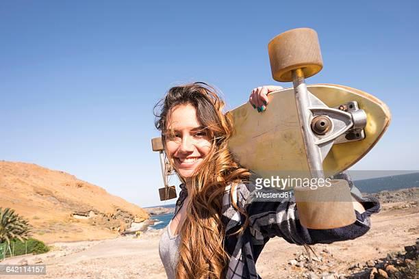 spain, portrait of smiling teenage girl with longboard on shoulders - longboard skating stock-fotos und bilder