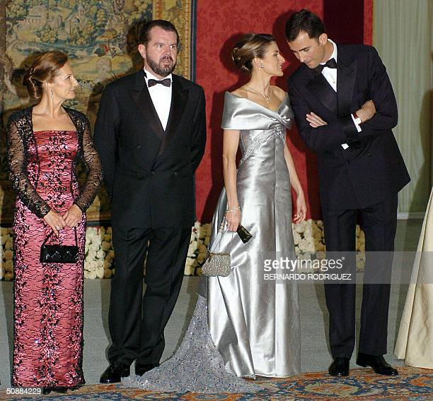 Prince Felipe of Spain talks to his fiancee Letizia Ortiz as they pose with Jesus Ortiz and Paloma Rocasolano at the Pardo Palace in Madrid for an...