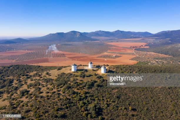 spain, province of ciudad real, puerto lapice, aerial view of three windmills standing on top of hill - castilla la mancha fotografías e imágenes de stock