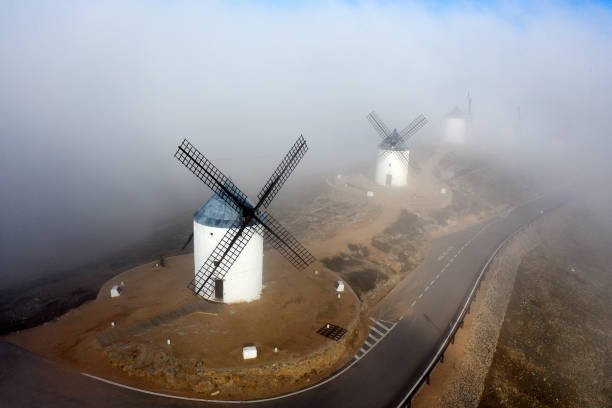 Spain, Province of Toledo, Consuegra, Aerial view of country road stretching past historical windmills during foggy weather