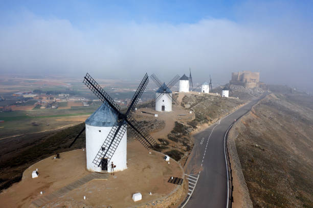 Spain, Province of Toledo, Consuegra, Aerial view of country road stretching past historical windmills