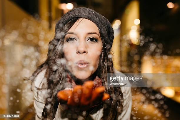 Spain, Reus, portrait of young woman blowing snow in the air at night