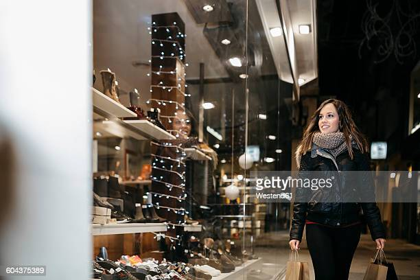 Spain, Reus, smiling young woman looking at window display in the evening