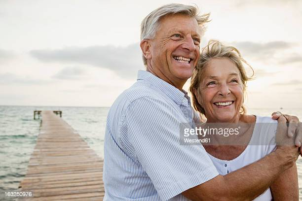 spain, senior couple embracing at the sea - mediterrane kultur stock-fotos und bilder