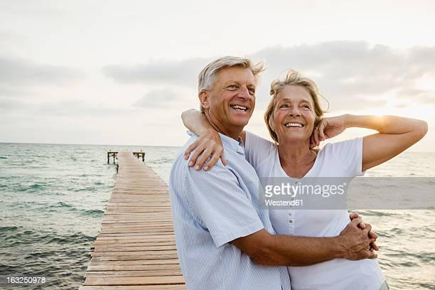Spain, Senior couple embracing at the sea